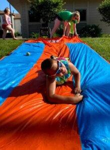 A camper slides down a slip and slide