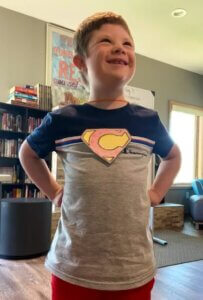 A young camper with a super hero shirt proudly poses in his super hero way